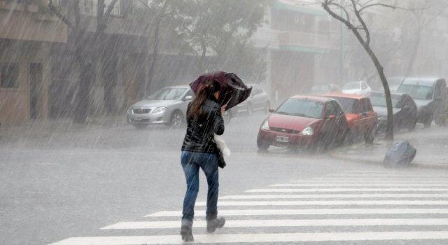 mujer en la calle con paraguas bajo la lluvia